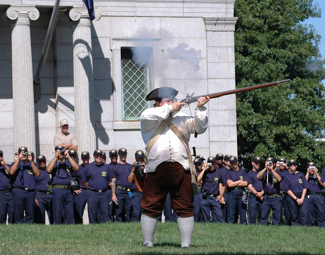 Chief petty officer (CPO) selectees watch a Revolutionary War-era rifle demonstration at the Bunker Hill Monument in Boston