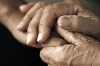 Genç birinin elini iki eli arasında tutan yaşlı bir insanın elleri