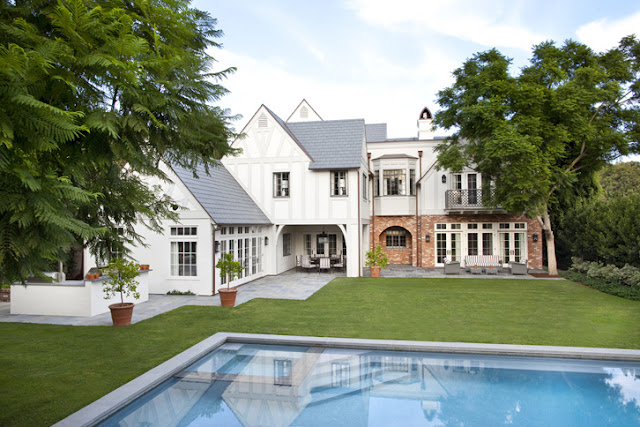 exterior of a white and brick Tudor home in Beverly Hills with a backyard, pool, and grass