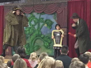 Young boy and two adults on stage acting out Jack and the Beanstalk