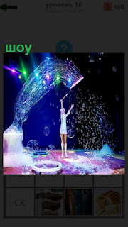 На сцене стоит девушка и показывает шоу с огнями и другими предметами
