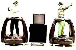 Image of two people within standing pods, with Virtuality head-sets. A 4 by 3 C.R.T. TV sits between them on castors.