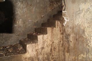 Eine alte Steintreppe führt in einem schmalen Schacht nach oben. Die Treppe ist mit Schutt bedeckt