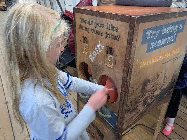 A girl putting her hand inside a box to feel what is inside