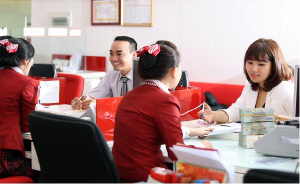 Nhân viên ngân hàng ở Bình Dương hướng dẫn khách hàng vay vốn