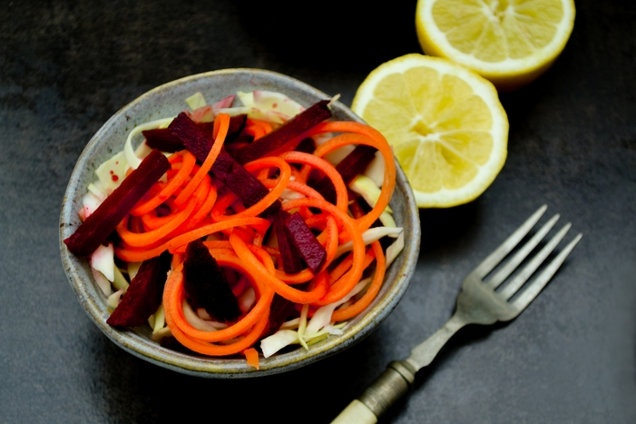 A simple Turkish salad of shredded white cabbage, carrots and beetroot sitting on a bed of salad leaves, dressed with a fruity pomegranate and lemon dressing. Utterly delicious! Don't be fooled by how simple this recipe is. It's a great one to have in your repertoire.