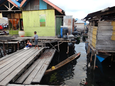 Nigel Foster photo, Dugout canoe with stilt houses above shallows Misool Indonesia