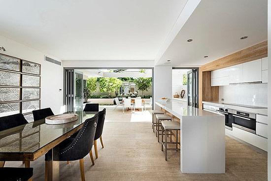 Bếp màu trắng tối giản với những món đồ gỗ màu ấm và không gian phòng ăn với những chiếc ghế màu đen tạo sự đối nghịch rõ nét.