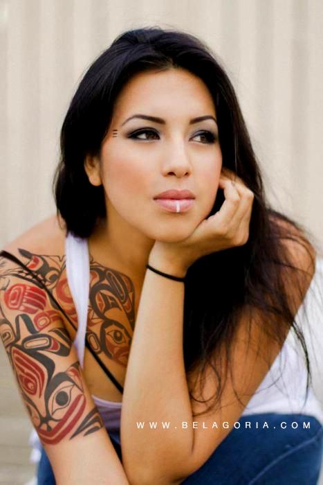 Fotografía de bella mujer India, con tatuajes Haida en el brazo