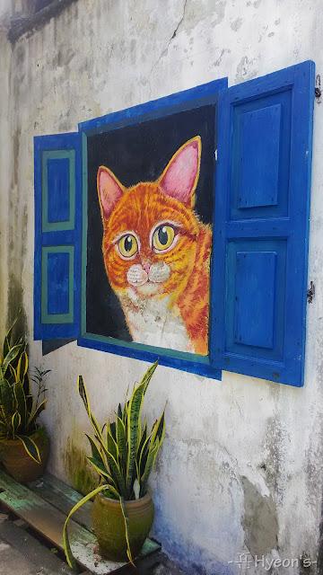 cat peeking from blue window street art penang