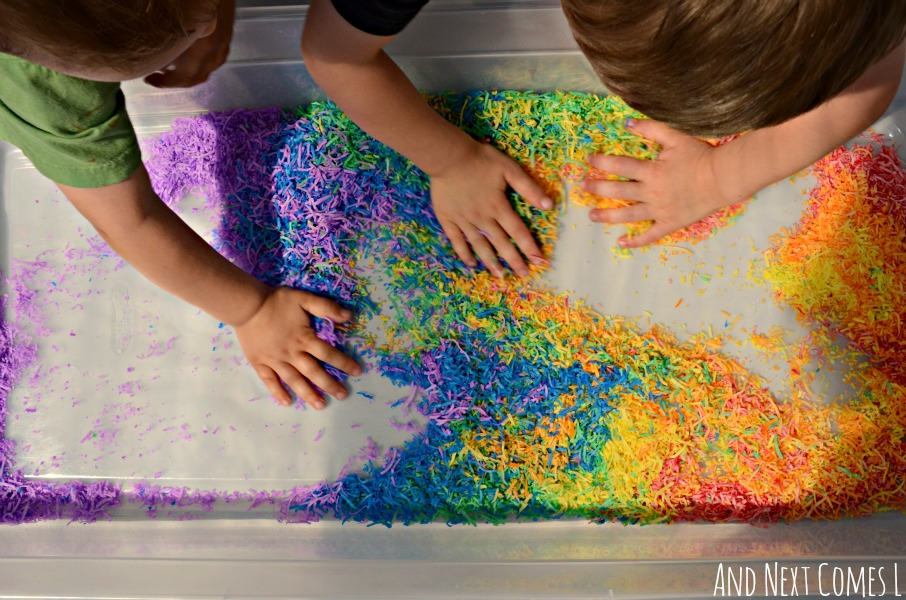 Playing with rainbow dyed shredded coconut - colorful, scented sensory play from And Next Comes L
