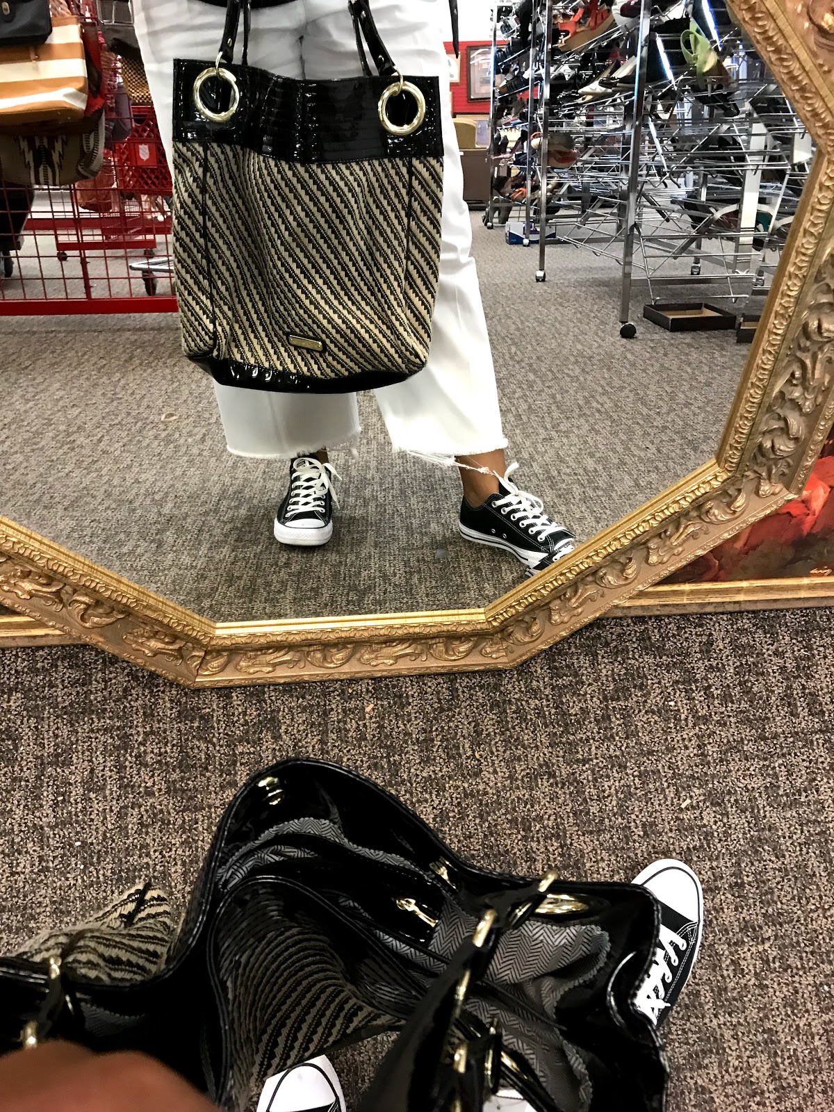 Woman looking in mirror holding handbag at The Salvation Army
