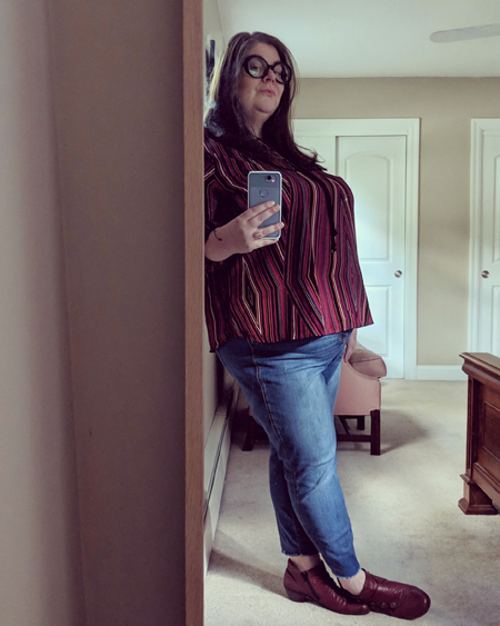 image of me standing in a full-length mirror, in profile, wearing large black glasses, a striped red top, blue jeans, and burgundy ankle boots