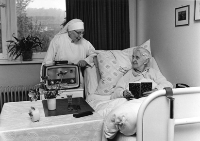 Bedroom in nursing home. Photo in black and white. An elderly woman in the bed, with a book, smiling. There's a nun in habit at bedside, also smiling, with a radio in front of her.