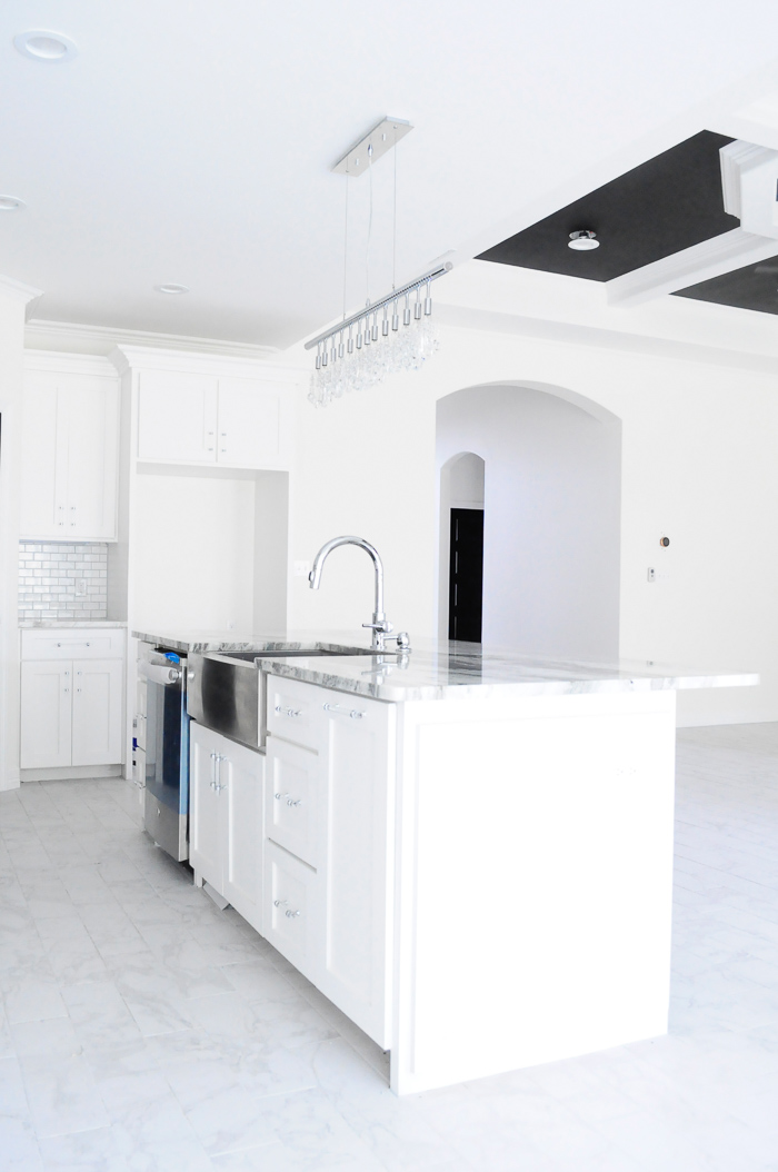 A large white kitchen and crystal chandelier in a new construction home with white walls.