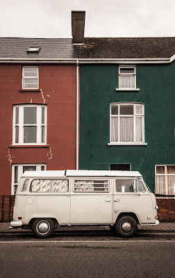 A white van parked in front of neighboring rowhomes, one red and one green.
