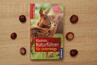 Man sieht ein Buch. Auf dem Buch sind zwei Rehe zu sehen, welche in die Kamera schauen. Darunter befindet sich ein roter Kasten, in dem der Buchtitel zu lesen ist. Rechts und links neben dem Buch liegen Kastanien.