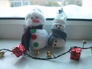 Két zokni hóember sállal a nyakában az ablakban ül karácsonyi díszítésként