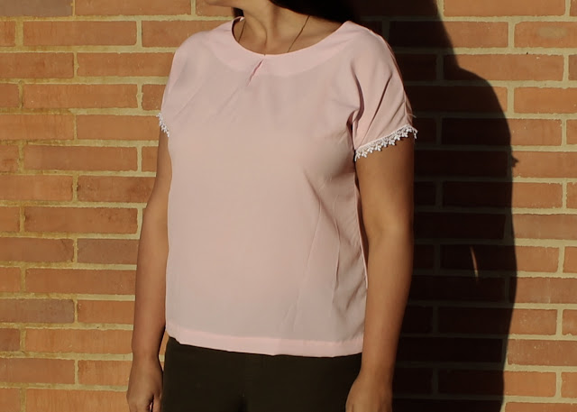 A woman wearing a pink crepe top made from the Avid Seamstress Drop-Sleeved Top sewing pattern.