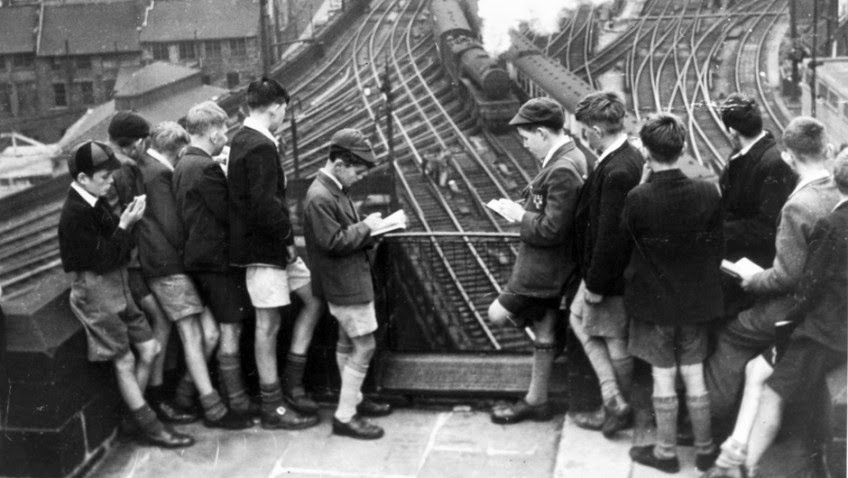 black and white photo of boys in short trousers old photo of boys on railway bridge watching trains go by