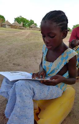 Aissata reading Tostan's children's books