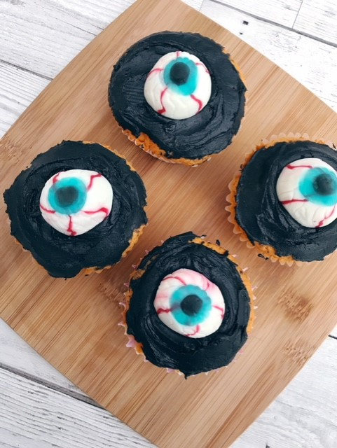 Four cupcakes on a wooden board with black icing and eyeball sweets in the centre