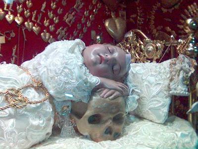 El Santo Niño de las Suertes recostado sobre la calavera.