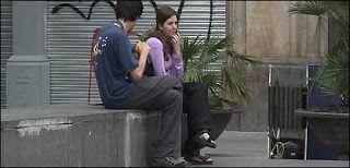 Pareja joven dialogando en una plaza