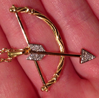Gold and diamond bow and arrow pendant by India Hicks.