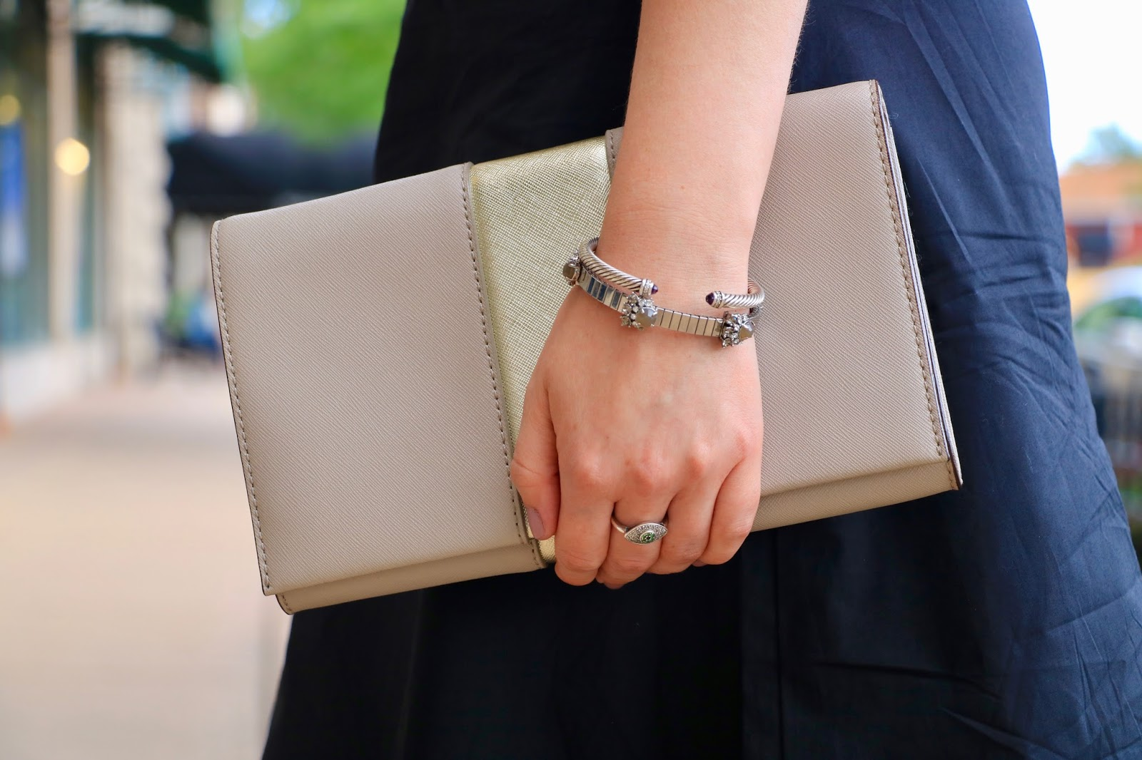 Fashion blogger Kathleen Harper of Kat's Fashion Fix carrying a gold Kate Spade clutch