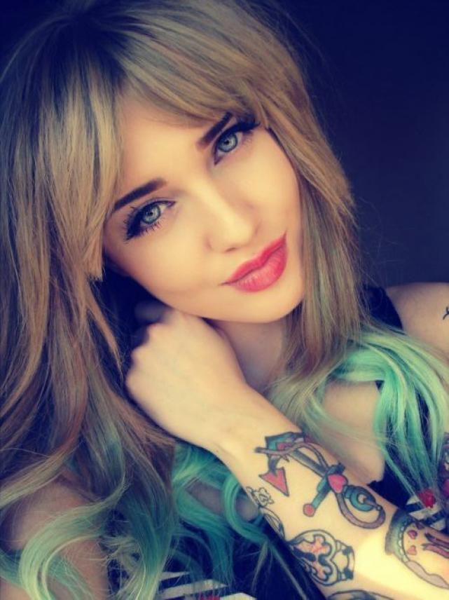 mujer de ojos azules y cara dulce, sorie tapandose el cuello, vemos en su antebrazo un tatuaje de ancla con nudos