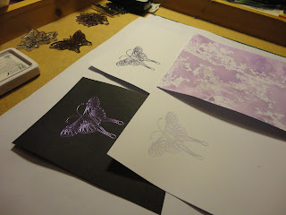 Four stamped butterfly images in shades of purple