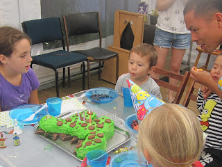 child blowing out 3 candles on dinosaur cake