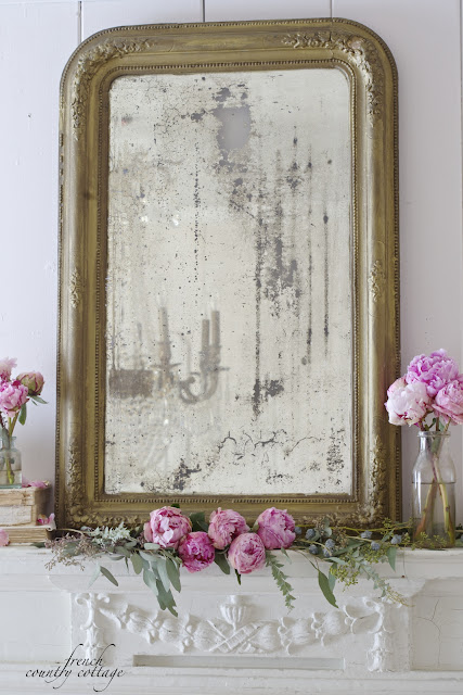Antique mirror on fireplace with flowers