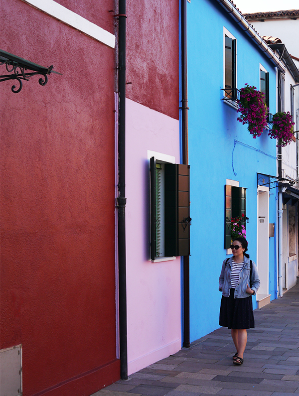 Walking past the colourful houses of Burano island in Venice, Italy