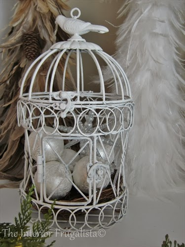 Bird cage filled with white snowflake ornaments