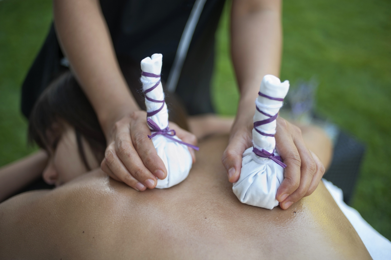a woman giving a thai massage with pindas, hot cloth bundles filled with herbs