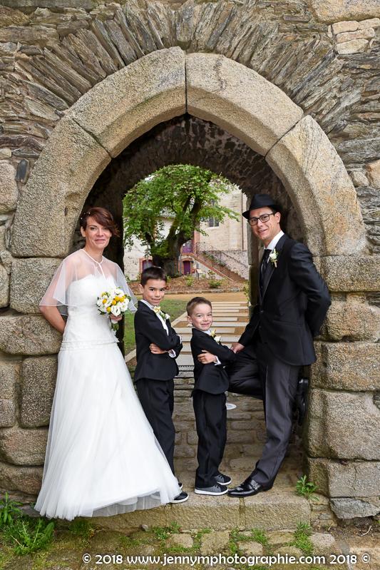 portrait mariés avec leurs enfants, photo de couple sous arche en pierre