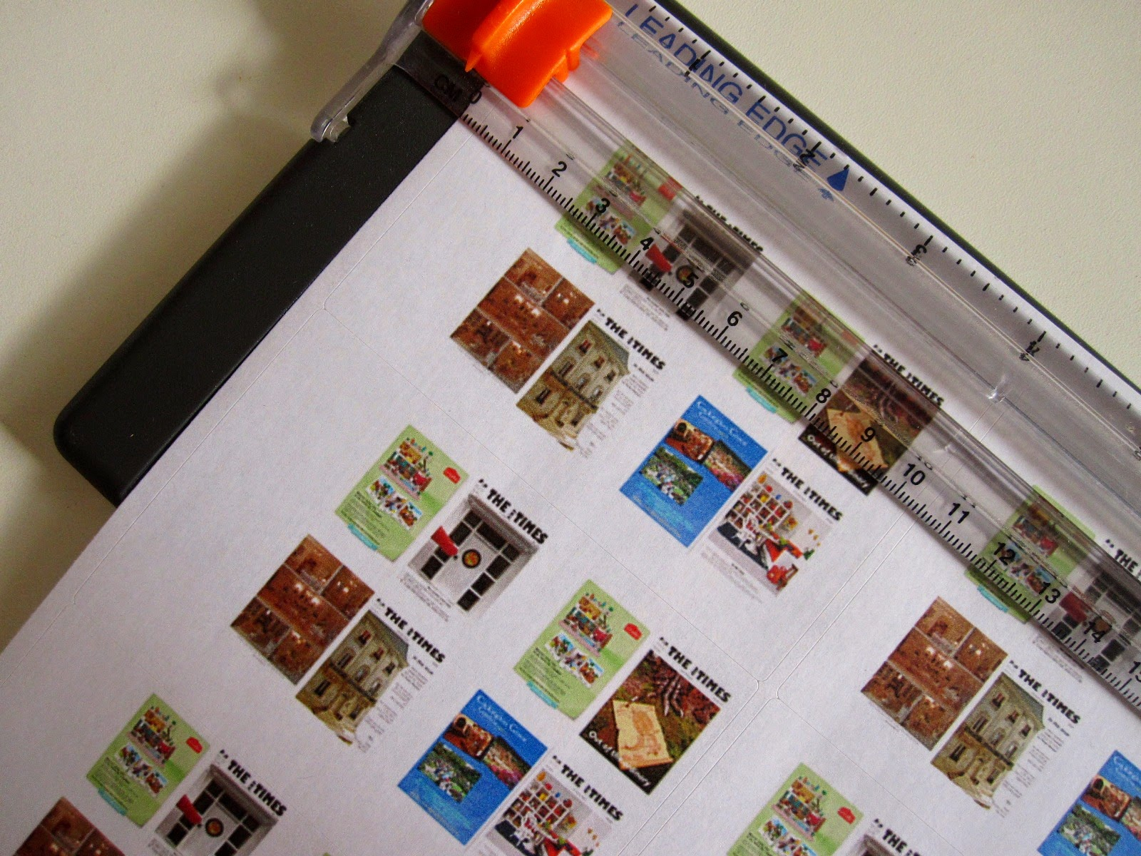 Sticker sheet printed with dolls house miniature versions of The tiny Times magazine, in a Fiskars cutter.