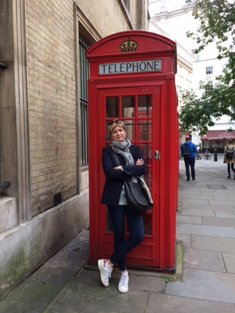 woman in jeans, blue jacket, sneakers and scarf in front of red phone box in London