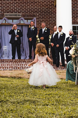 K'Mich Weddings - wedding planning - flower girl walking in a white dress