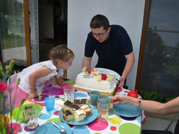 Przyjęcie urodzinowe na tarasie - kolorowe ceraty, zastawa i Zosia dmuchająca świeczki