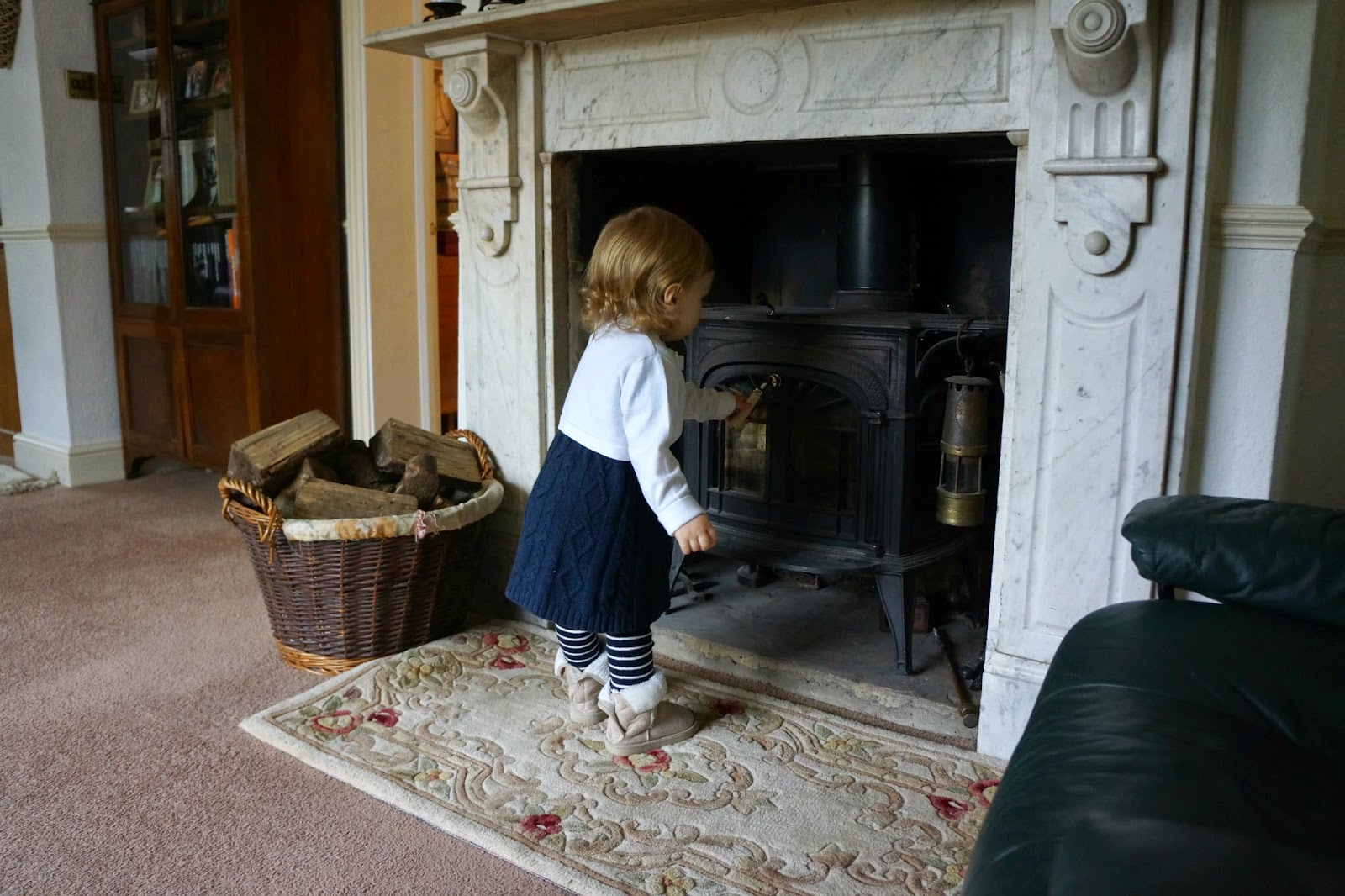toddler looking at a fireplace