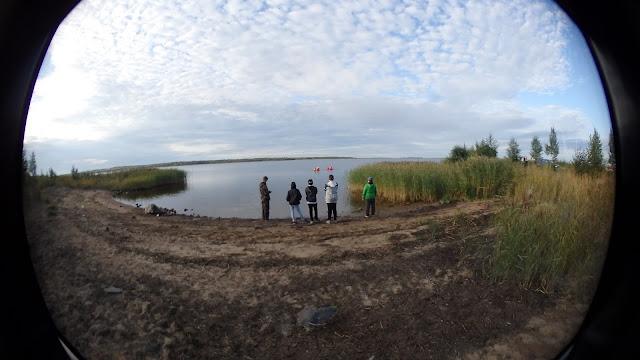 Viisi nuorta seisovat rannalla ja katsovat vedessä kahlaajia.