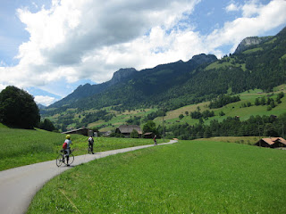 Cyclists along a rural road, with blue skies and puffy clouds over the hills, en route to Lenk im Simmental, Switzerland
