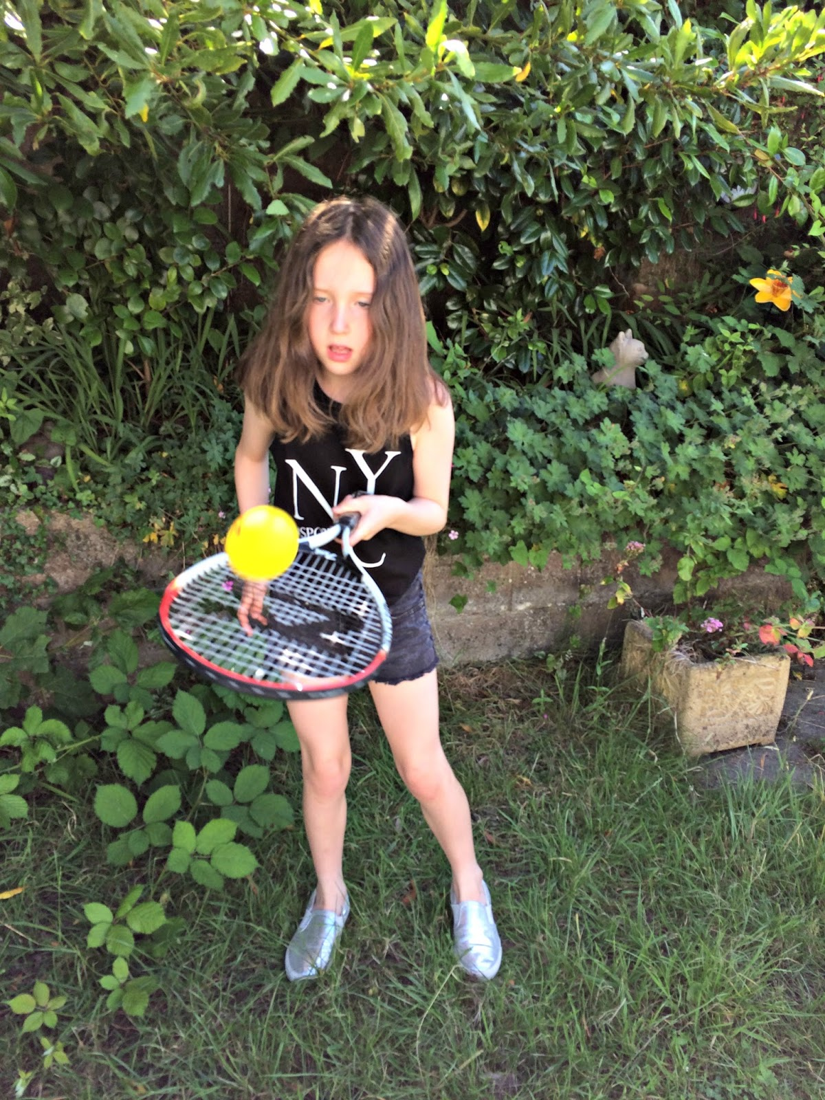 Caitlin balancing a tennis ball on her racquet