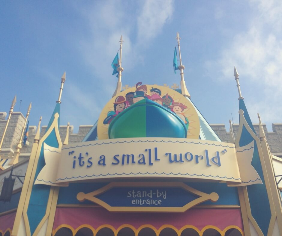 "A photo of the entrance to ""it's a small world"" in Magic Kingdom, Walt Disney World. The camera looks up at the castle style spires on top of the entrance sign, blue flags fly from the top most spires. A blue sky is spotted with whispy white clouds. Image for ""How to get a much-needed rest at Magic Kingdom""."