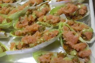 Barquitas de endivias rellenas de salmón con cebolla confitada y mayonesa de ajo.