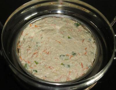 Batter plate put in a steamer to make rava veggie dhokla