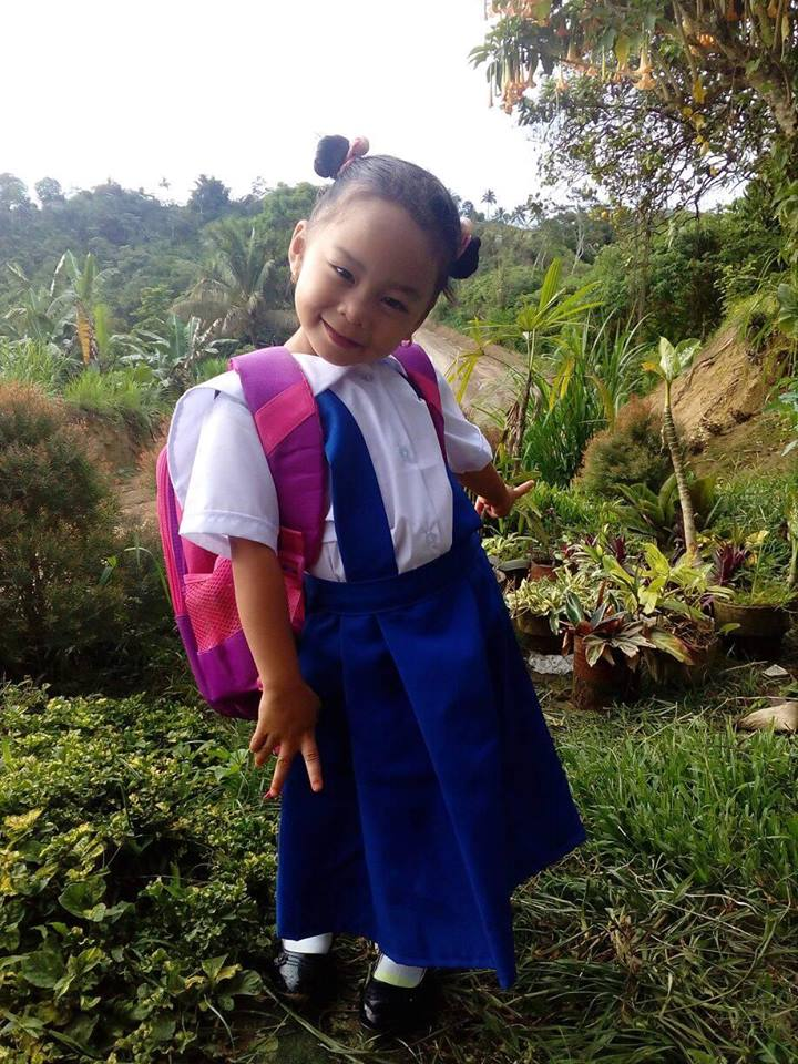 school girl's charming smile despite muddy uniform brings good fortune to town